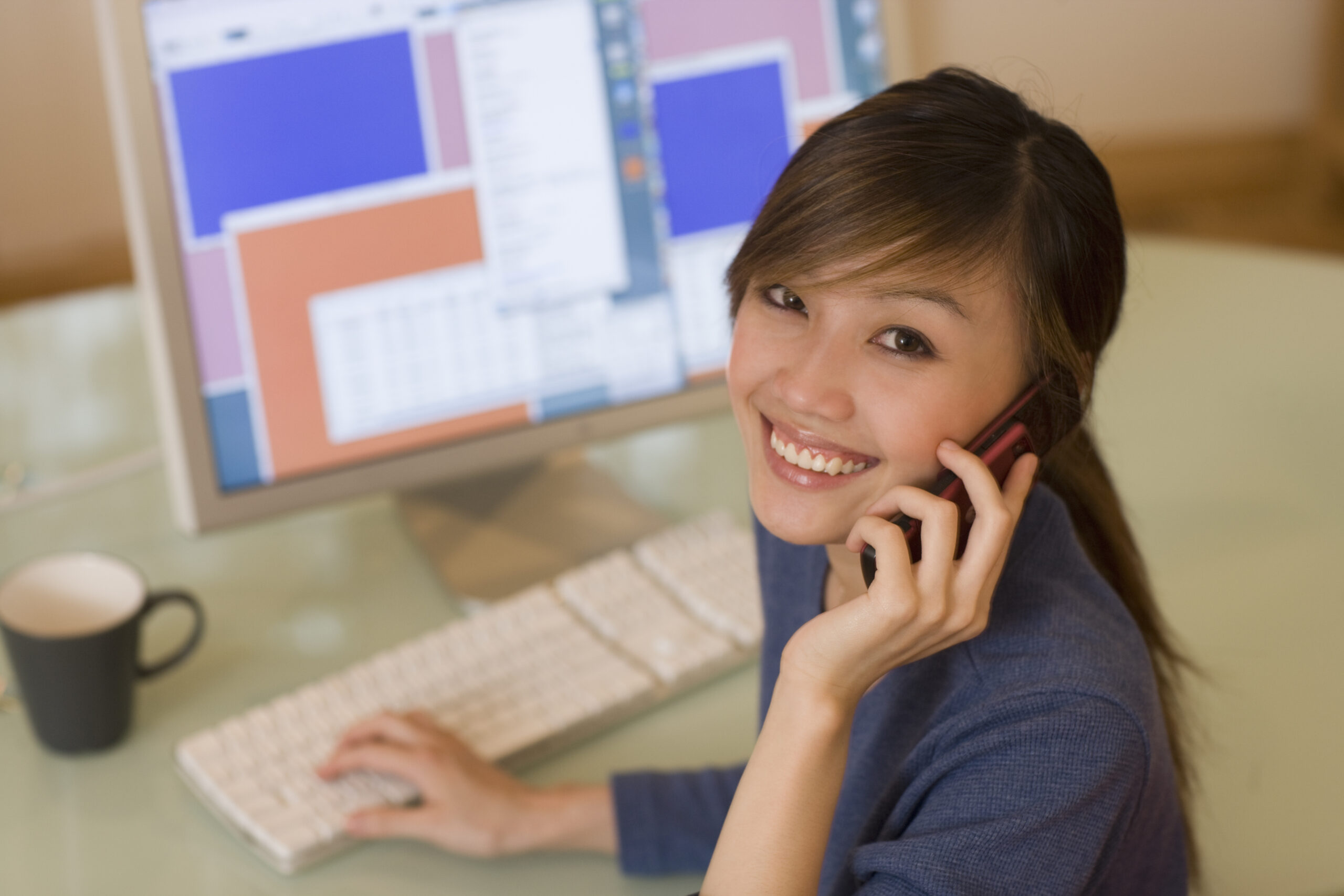 attractive young Asian woman working at the computer